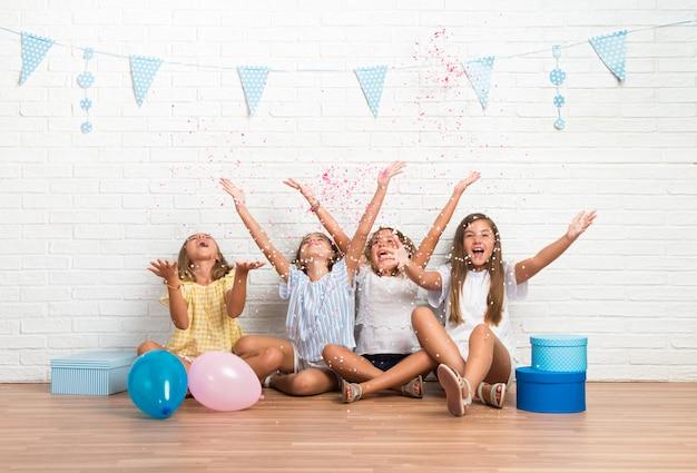Gruppe freunde in einer geburtstagsfeier, die mit konfettis spielt Premium Fotos