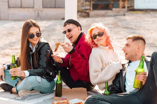 Gruppe freunde mit dem bier und pizza, die spaß haben, draußen zu sitzen Kostenlose Fotos