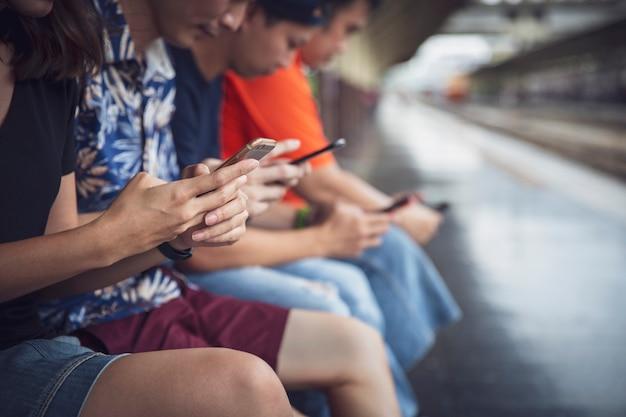 Gruppe freunde, welche die digitalen smartphones im freien mit dem haben des spaßes mit technologietrends verwenden Premium Fotos