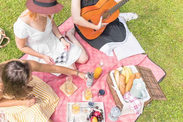 Gruppe freundinnen, die im picknick sitzt auf decke genießen Kostenlose Fotos