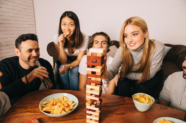 Gruppe frohe freunde, die tabletopspiel spielen Kostenlose Fotos
