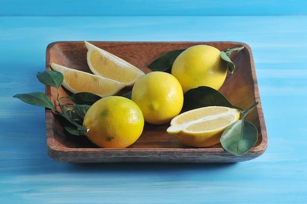 Gruppe gelbe zitronen mit blättern auf einer quadratischen hölzernen platte Premium Fotos