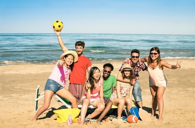 Gruppe gemischtrassige glückliche freunde, die spaß mit strandsportspielen haben Premium Fotos