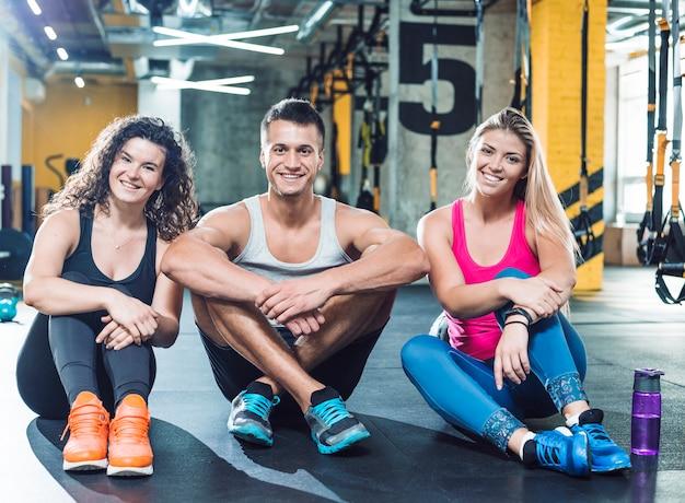 Gruppe glückliche athletische leute, die auf boden in der turnhalle sitzen Kostenlose Fotos