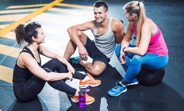 Gruppe glückliche athletische leute, die auf boden nach training im fitnessstudio sitzen Kostenlose Fotos