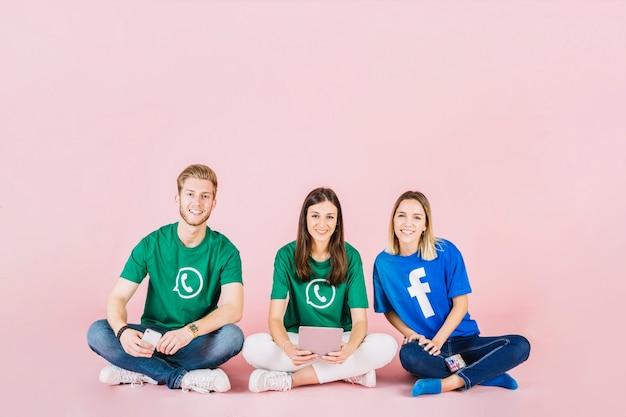 Gruppe glückliche freunde, die auf rosa hintergrund sitzen Kostenlose Fotos