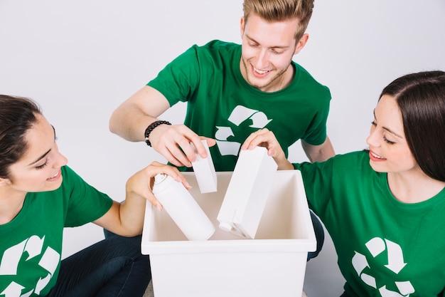 Gruppe glückliche freunde, die flaschen im weißen mülleimer werfen Kostenlose Fotos
