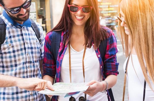 Gruppe glückliche freunde, die nach richtung in karte suchen Kostenlose Fotos