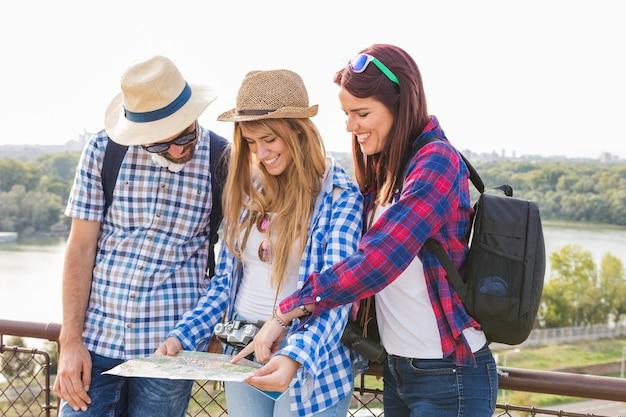 Gruppe glückliche freunde, die nach standort in der karte suchen Kostenlose Fotos