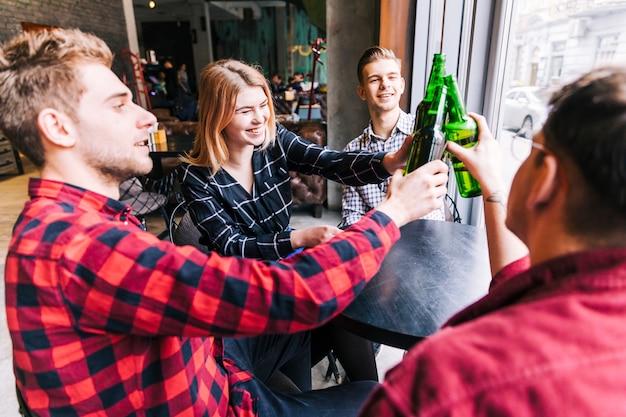 Gruppe glückliche freunde, die um den holztisch rösten die grünen bierflaschen in der kneipe sitzen Kostenlose Fotos