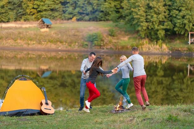 Gruppe glückliche freunde mit gitarre, spaß im freien habend, tanzen und springen nahe dem see im park Premium Fotos