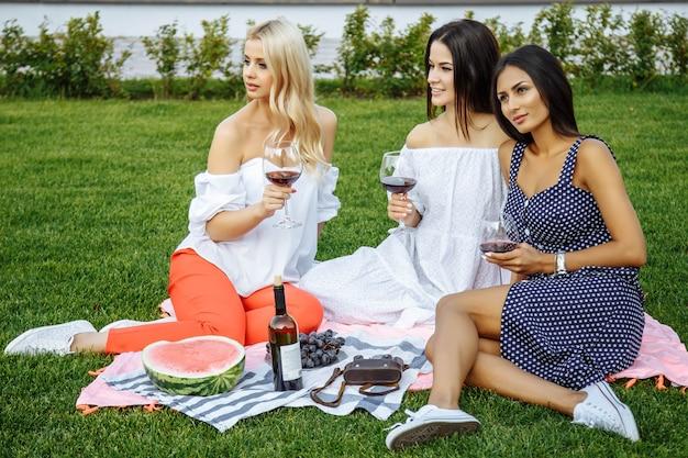 Gruppe glückliche junge freunde im urlaub, die wein am picknick genießen. Premium Fotos
