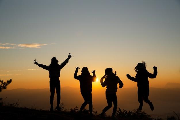 Gruppe glückliche junge leute, die auf den hügel springen. junge frauen genießen Kostenlose Fotos