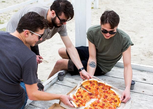 Gruppe glückliche leute mit pizza auf rest Kostenlose Fotos