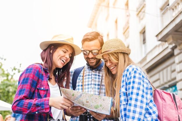 Gruppe glückliche männliche und weibliche wanderer, die nach standort in der karte suchen Kostenlose Fotos