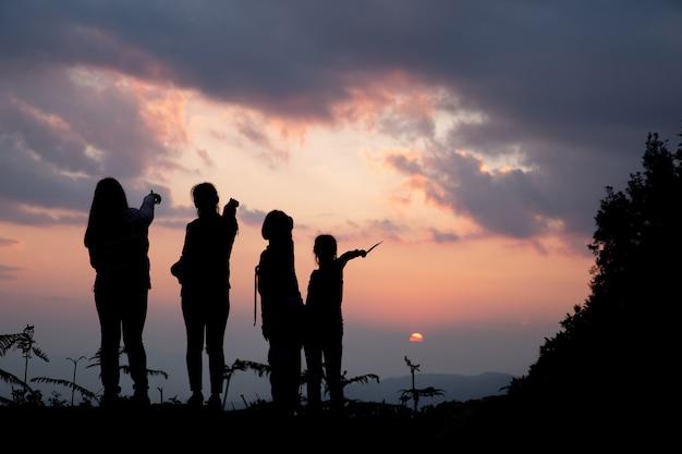 Gruppe glückliche menschen, die am sommersonnenuntergang in der natur spielen Kostenlose Fotos