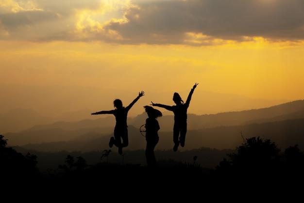 Gruppe glückliche menschen, die in den berg bei sonnenuntergang springen Kostenlose Fotos