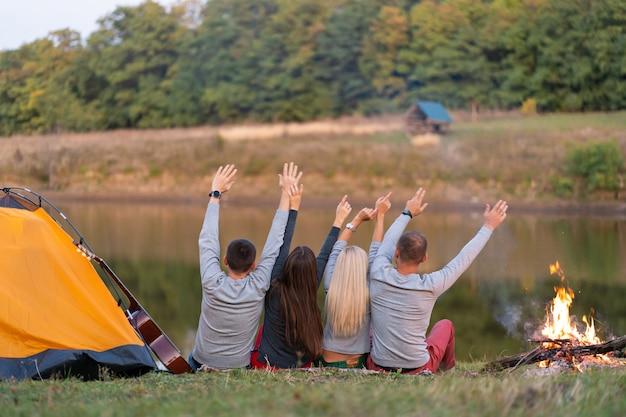 Gruppe glücklicher freunde, die am flussufer kampieren, halten hände hoch und genießen ansicht tanzen. Premium Fotos