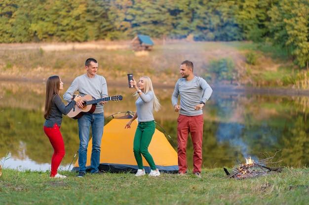 Gruppe glücklicher freunde mit gitarre, spaß im freien, tanzen und springen Premium Fotos