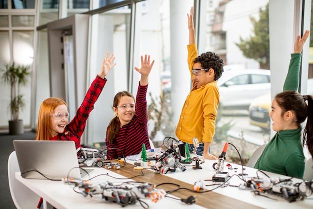 Gruppe glücklicher kinder, die elektrisches spielzeug und roboter im robotikklassenzimmer programmieren Premium Fotos