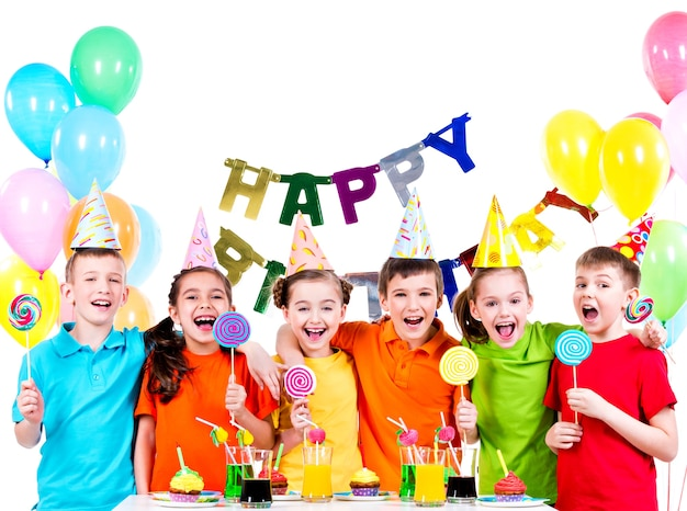 Gruppe glücklicher kinder mit bunten bonbons, die spaß an der geburtstagsfeier haben - lokalisiert auf einem weiß. Kostenlose Fotos