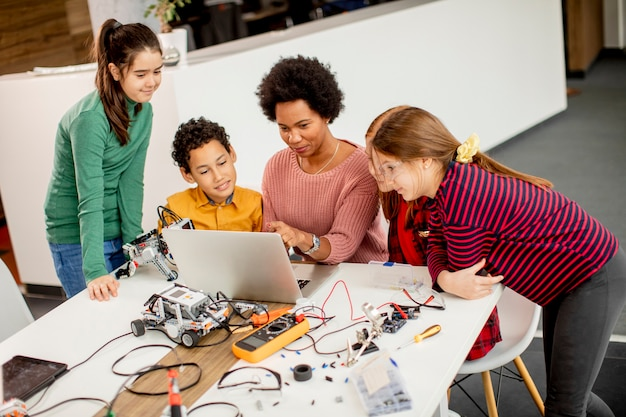Gruppe glücklicher kinder mit ihrer afroamerikanischen wissenschaftslehrerin mit laptop, der elektrisches spielzeug und roboter am robotikklassenzimmer programmiert Premium Fotos
