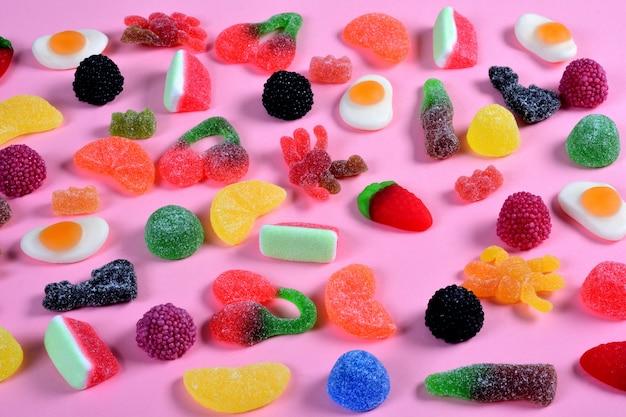 Gruppe gummiartige süßigkeiten auf rosa Premium Fotos
