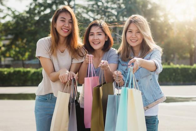 Gruppe junge asiatin beim einkaufen in einem markt im freien mit einkaufstüten in ihren händen Kostenlose Fotos