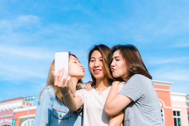Gruppe junge asiatinnen selfie sich mit einem telefon in einer pastellstadt nach dem einkauf Kostenlose Fotos