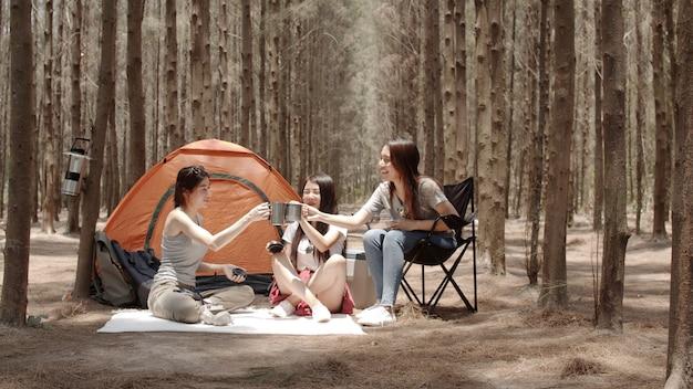 Gruppe junge asiatische freunde, die zusammen im wald kampieren oder picknicken Kostenlose Fotos