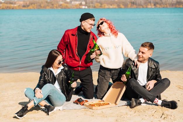 Gruppe junge freunde auf picknick an der küste Kostenlose Fotos