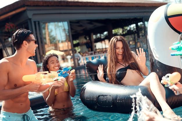 Gruppe junge lächelnde freunde, die spaß im pool haben Premium Fotos
