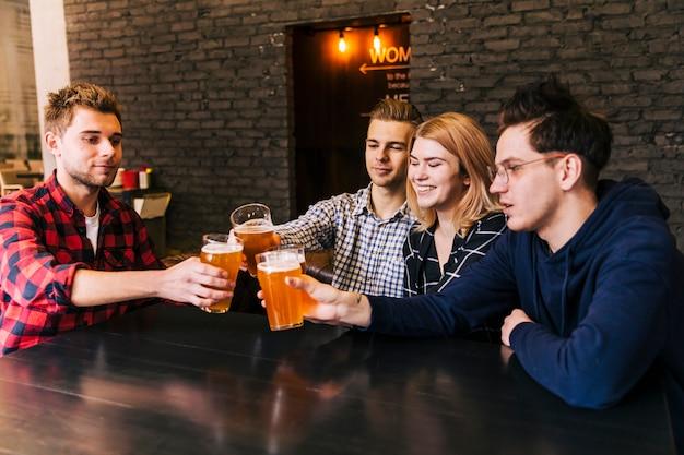 Gruppe junge leute, die am barrestaurant zujubeln Kostenlose Fotos