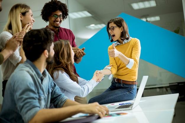 Gruppe junge mitarbeiter, die um einen tisch und ein händeschütteln im büro aufeinander einwirken Premium Fotos
