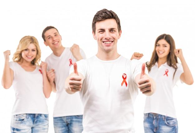 Gruppe junge positive leute mit rotem band. Premium Fotos