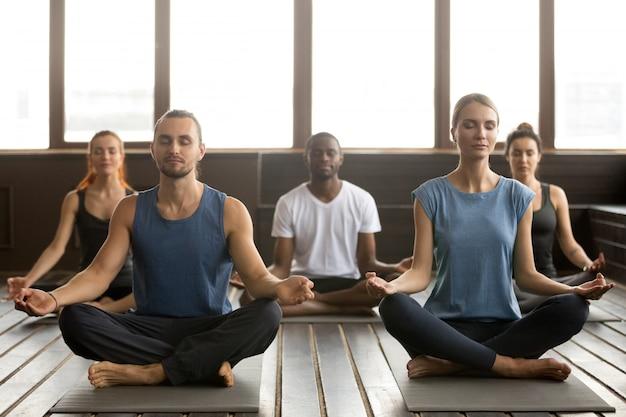 Gruppe junge sportliche leute, die in sukhasana sitzen, trainieren Kostenlose Fotos