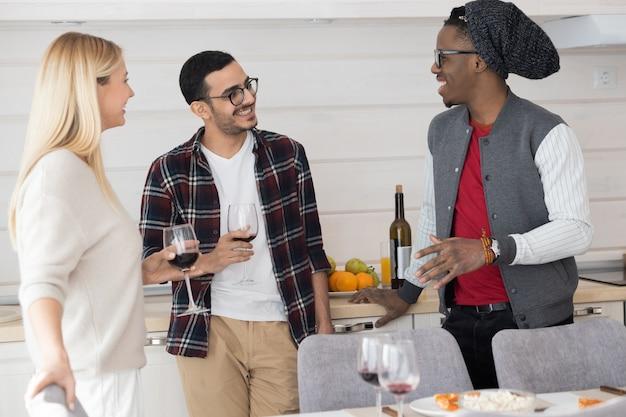 Gruppe junger freunde, die wein trinken und afroamerikaner auf hausparty hören Premium Fotos