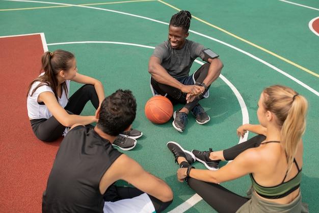 Gruppe junger freundlicher interkultureller leute, die auf spielplatz sitzen, während sie sich für ein anderes basketballspiel vorbereiten Premium Fotos