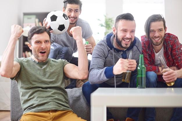 Gruppe junger männer, die ein match im fernsehen ansehen Kostenlose Fotos