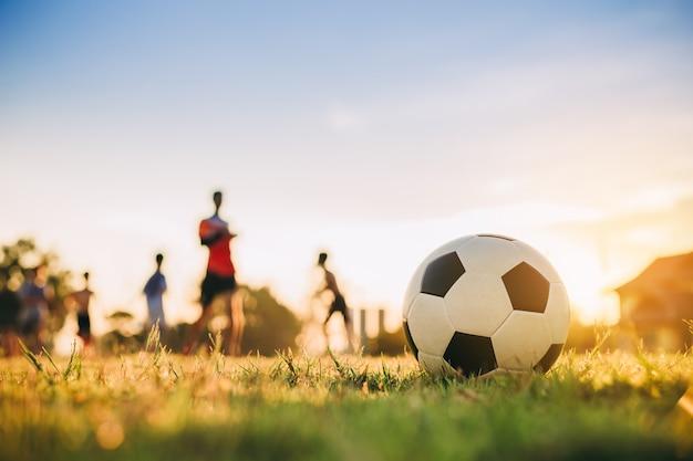 Gruppe kinder, die fußballfußball spielen Premium Fotos