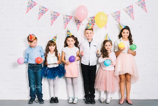 Gruppe kinder, die gegen die wand hält ballone in der hand an der geburtstagsfeier stehen Kostenlose Fotos