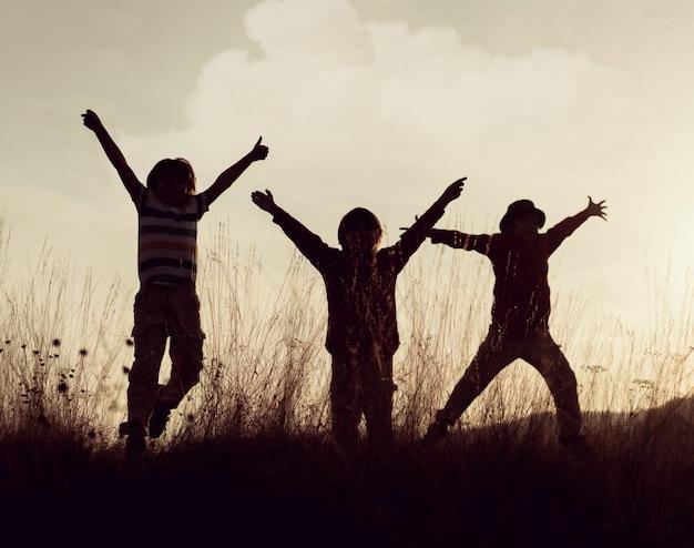 Gruppe kinder, die ihre zeit auf der wiese während des sonnenuntergangs genießen Premium Fotos