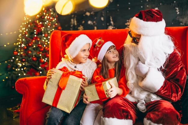 Gruppe kinder, die mit sankt und geschenken auf weihnachtsabend sitzen Kostenlose Fotos