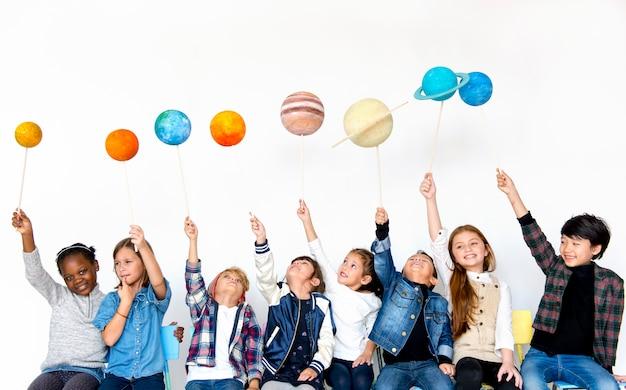 Gruppe kinder, die papercraft-galaxisymbol auf weißem blackground halten Premium Fotos