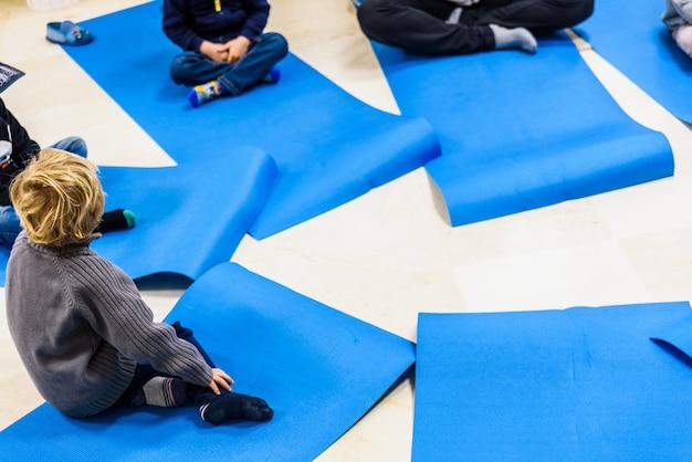 Gruppe kinder, die yogaübungen tun und auf irgendeiner matte sich entspannen. Premium Fotos