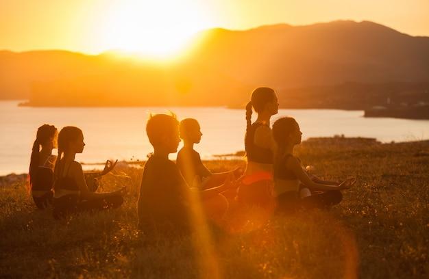 Gruppe kinder nehmen an yoga mit einem trainer auf dem ozean teil. Premium Fotos
