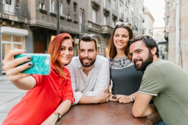 Gruppe lächelnde erwachsene freunde, die zusammen selfie nehmen Kostenlose Fotos