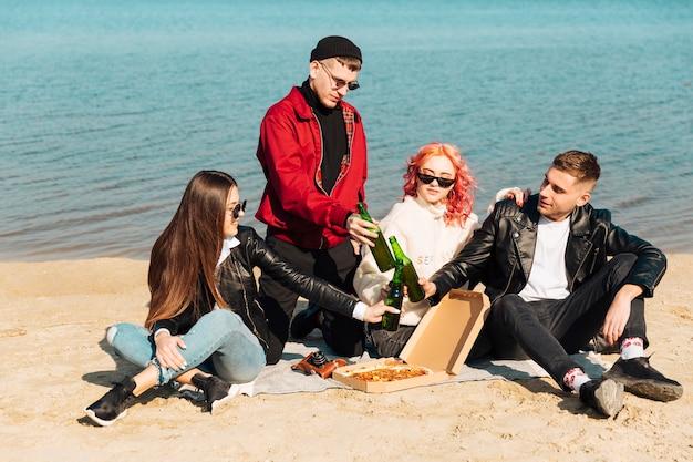 Gruppe lächelnde freunde auf picknick am strand Kostenlose Fotos