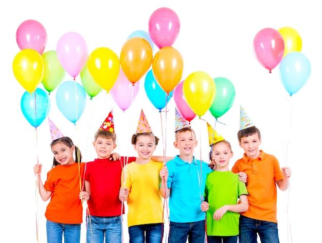 Gruppe lächelnder kinder in den farbigen t-shirts und in den parteihüten mit luftballons auf einem weißen hintergrund Kostenlose Fotos