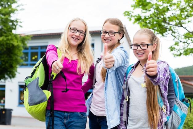 Gruppe mädchen, die vor schule stehen Premium Fotos